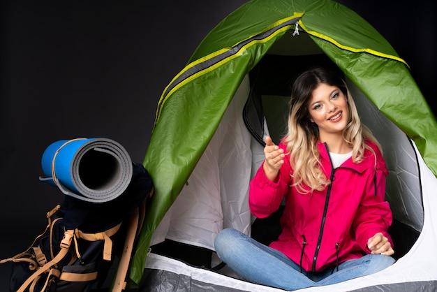 Donna dell'adolescente dentro una tenda verde di campeggio isolata sulla parete nera che stringe le mani per chiudere molto