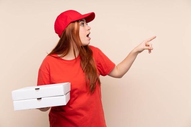 Donna dell'adolescente di consegna della pizza che tiene una pizza che indica il dito il lato