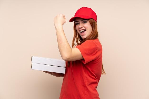 Donna dell'adolescente di consegna della pizza che tiene una pizza sopra la parete isolata che fa forte gesto