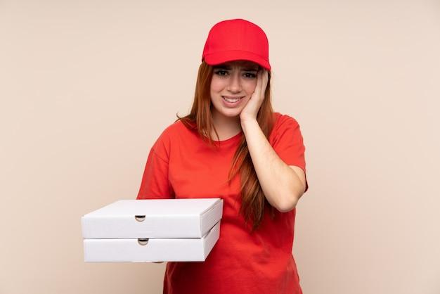 Donna dell'adolescente di consegna della pizza che tiene una pizza sopra la parete isolata infelice e frustrata con qualcosa. espressione facciale negativa