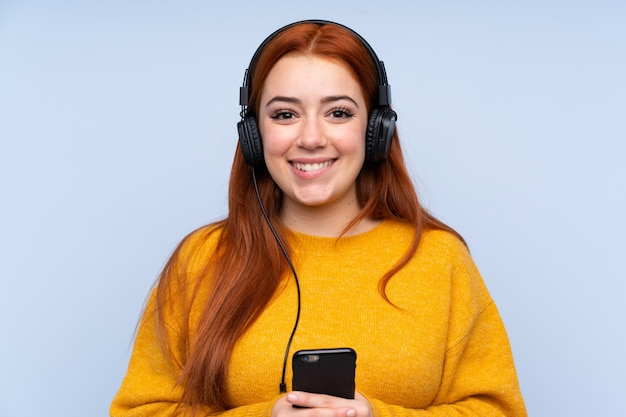 Donna dell'adolescente di redhead che ascolta la musica con un cellulare e che sembra anteriore