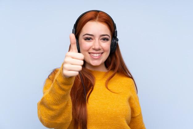 Donna dell'adolescente di redhead che ascolta la musica e con il pollice in su