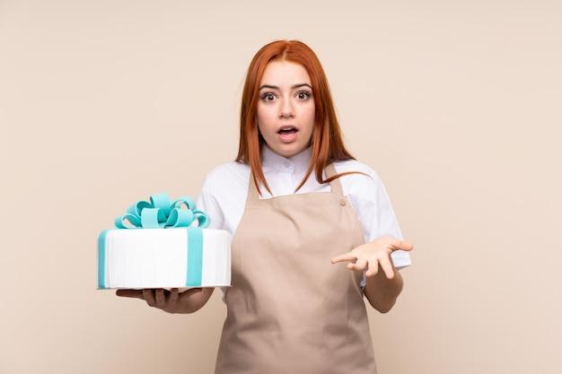 Donna dell'adolescente di redhead con una grande torta con espressione facciale colpita