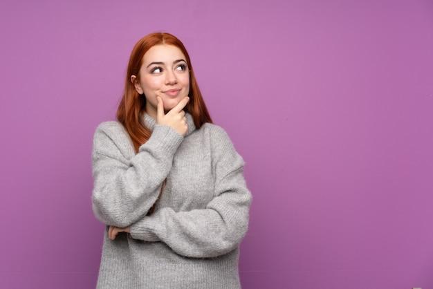 Donna dell'adolescente di redhead sopra la parete viola isolata che pensa un'idea