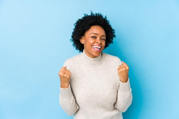 Donna dell'afroamericano di mezza età contro una parete blu isolata incoraggiante spensierata ed eccitata. concetto di vittoria.