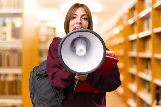 Donna dell'allievo che tiene un megafono su sfondo sfocato. di nuovo a scuola