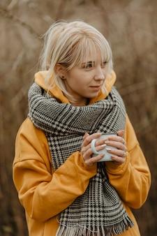 Donna dell'angolo alto che beve tè per riscaldarsi