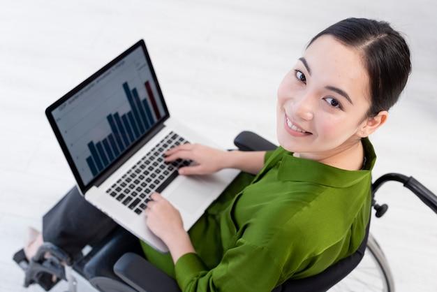 Donna dell'angolo alto che lavora al computer portatile
