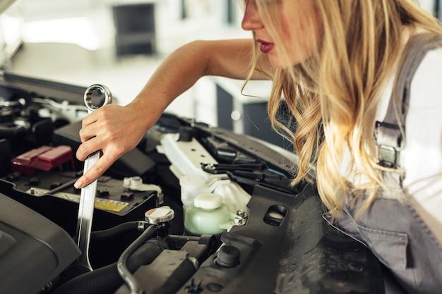 Donna dell'angolo alto che ripara il motore di automobile