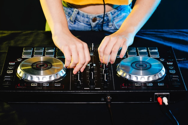 Donna dell'angolo alto in controllo del miscelatore del dj