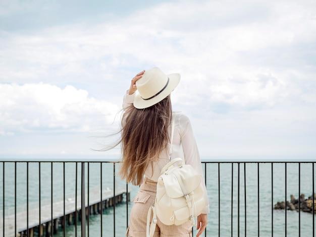 Donna dell'angolo alto in riva al mare