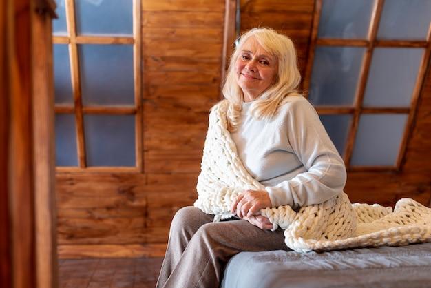 Donna dell'angolo alto sul bordo sul letto