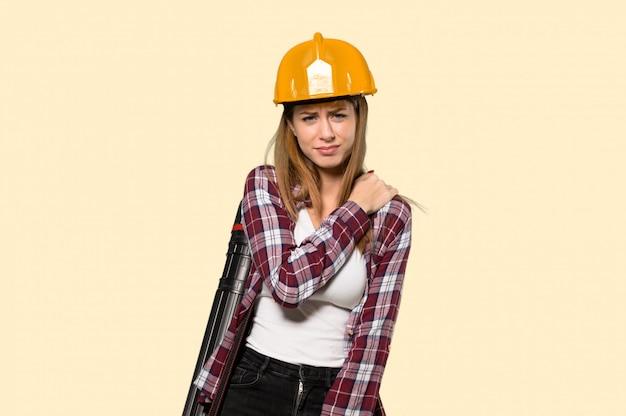 Donna dell'architetto che soffre dal dolore alla spalla per aver fatto uno sforzo sopra la parete gialla isolata