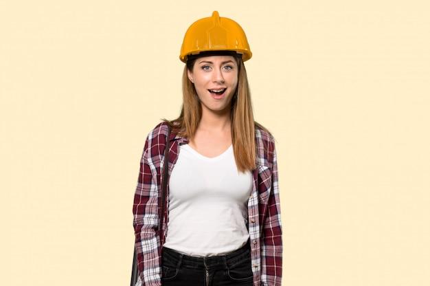 Donna dell'architetto con espressione facciale di sorpresa sopra giallo isolato