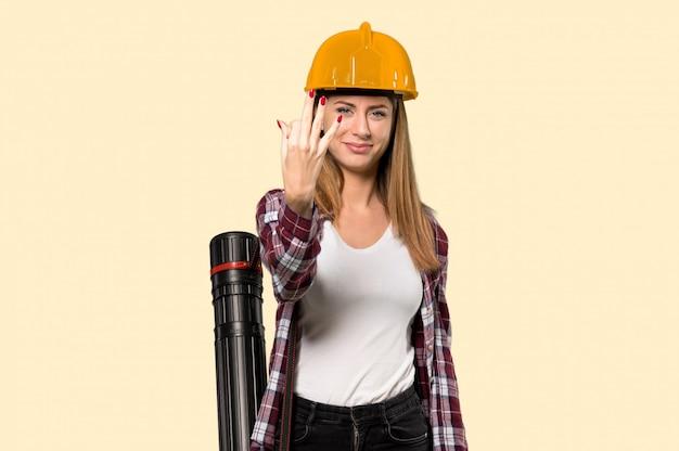 Donna dell'architetto felice e che conta tre con le dita sopra giallo isolato