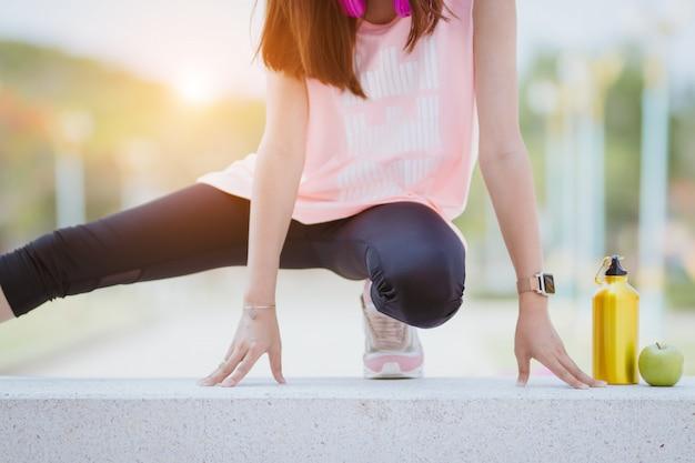 Donna dell'asia che allunga muscolo prima e dopo l'esercizio