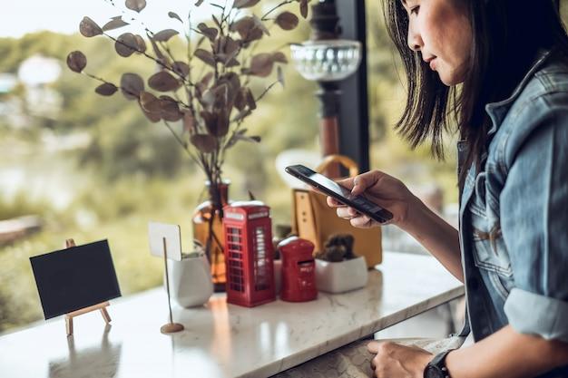 Donna dell'asia che si siede nella caffetteria e che utilizza telefono cellulare