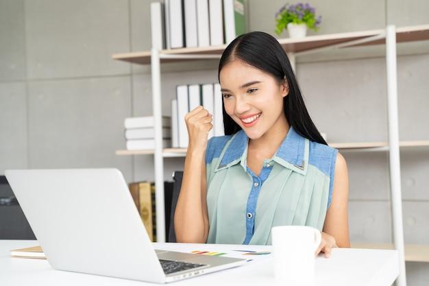 Donna dell'asia con il computer portatile che celebra il concetto di successo