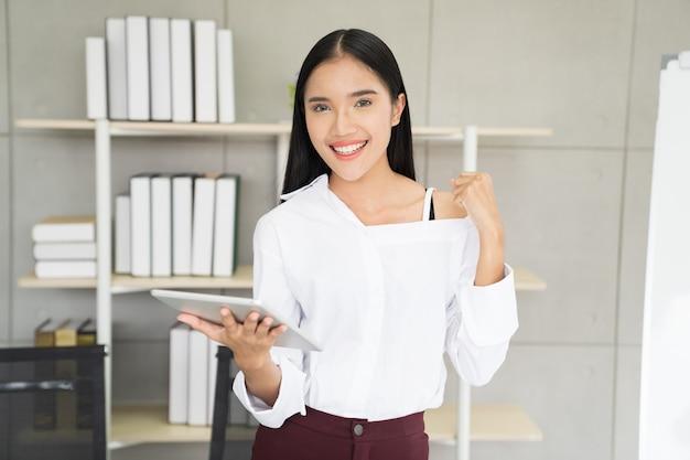 Donna dell'asia con la compressa che celebra il concetto di successo