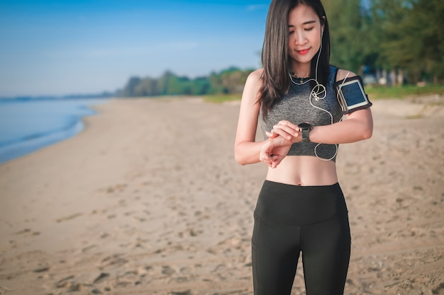 Donna dell'asia negli articoli di sport che gode per l'esercizio e correre sulla spiaggia.