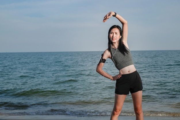 Donna dell'asia negli articoli di sport che si esercita e che corre sulla spiaggia.