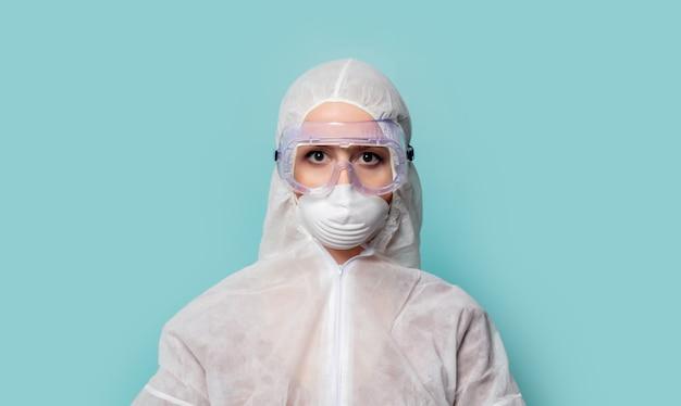 Donna dell'erba medica che indossa abbigliamento protettivo contro il virus su un fondo blu