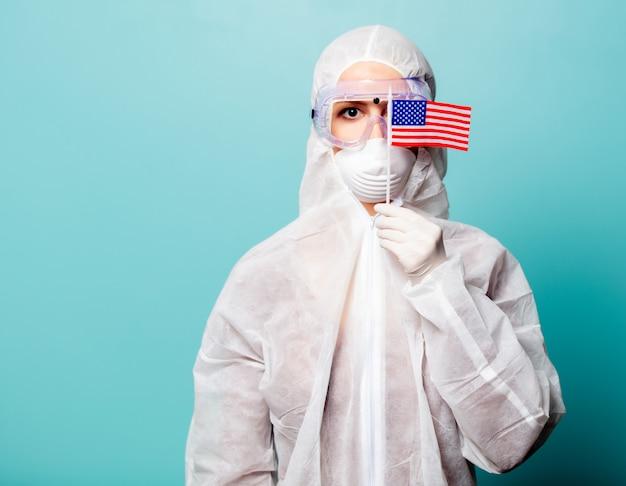 Donna dell'erba medica che indossa indumenti protettivi contro il virus con la bandiera degli stati uniti d'america su un fondo blu