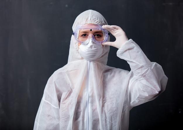 Donna dell'erba medica che indossa indumenti protettivi contro il virus
