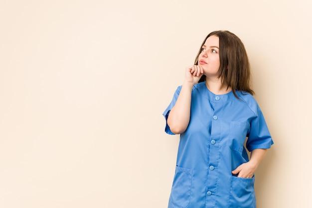 Donna dell'infermiera dei giovani che osserva lateralmente con l'espressione dubbiosa e scettica.