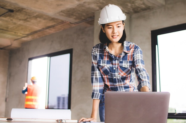 Donna dell'ingegnere che esamina computer circa la costruzione progressiva