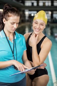 Donna dell'istruttore che mostra lavagna per appunti ad un nuotatore allo stagno