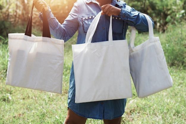 Donna della borsa di totalizzatore del cotone della tenuta della mano tre sul fondo dell'erba verde. concetto di eco e riciclaggio