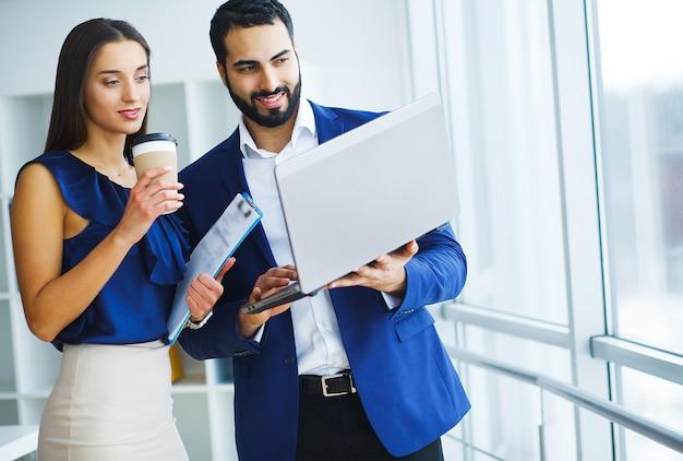 Donna della corsa abbastanza mista e il suo collega barbuto che utilizza computer portatile per discutere progetto comune nella società dell'ufficio