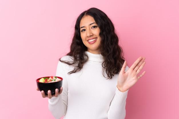 Donna della corsa mista che giudica una ciotola piena di tagliatelle sopra la parete rosa isolata che saluta con la mano con l'espressione felice