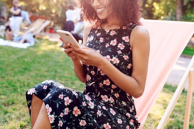Donna della corsa mista con i capelli ricci che si rilassano nel parco di estate nel fine settimana soleggiato