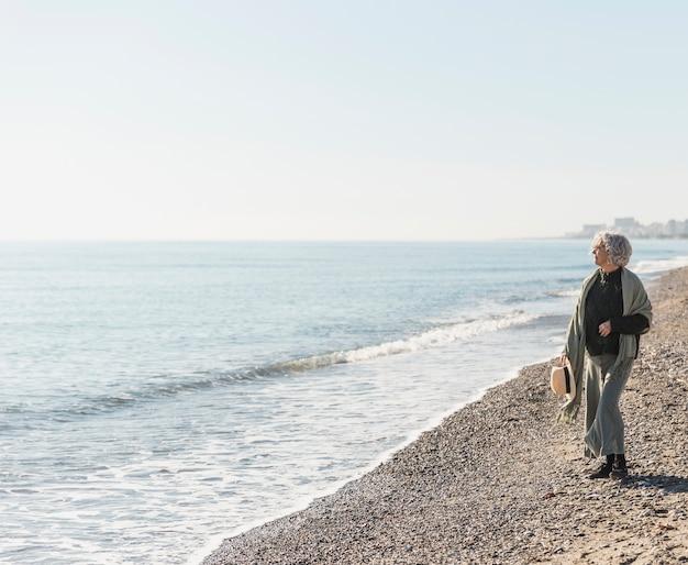 Donna della foto a figura intera che cammina sulla spiaggia