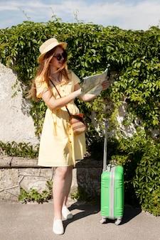Donna della foto a figura intera che esamina mappa