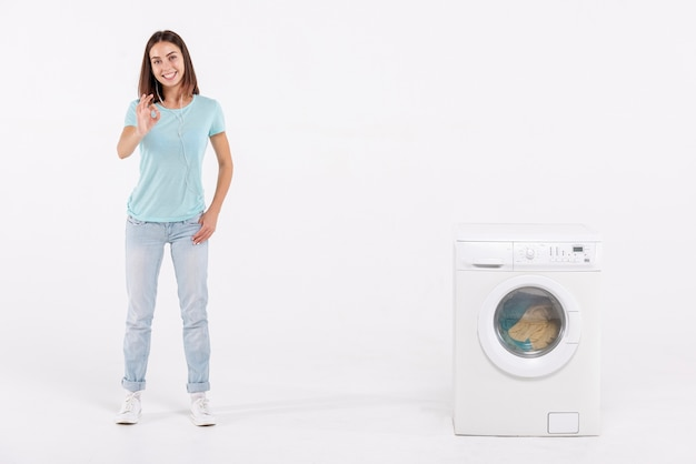 Donna della foto a figura intera che esprime approvazione con la lavatrice