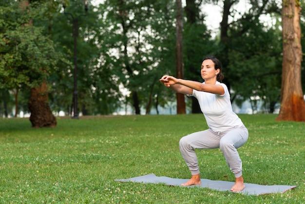 Donna della foto a figura intera che fa gli edifici occupati sulla stuoia di yoga