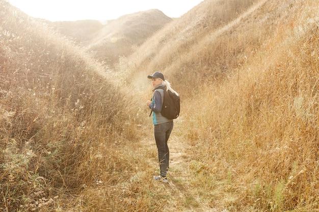 Donna della foto a figura intera che fa un'escursione nella regione selvaggia