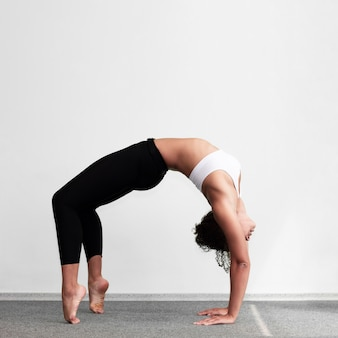 Donna della foto a figura intera che fa un esercizio di ginnastica complesso