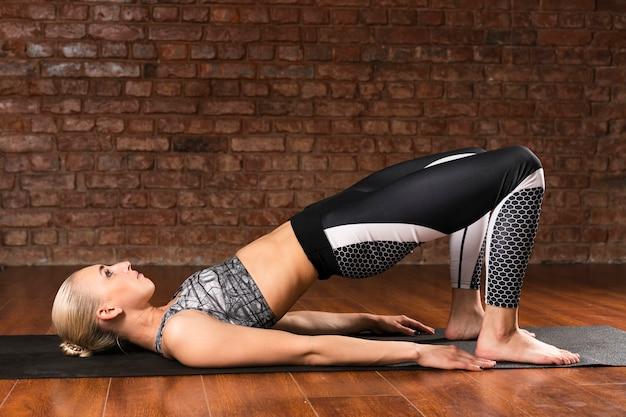 Donna della foto a figura intera che fa yoga a casa