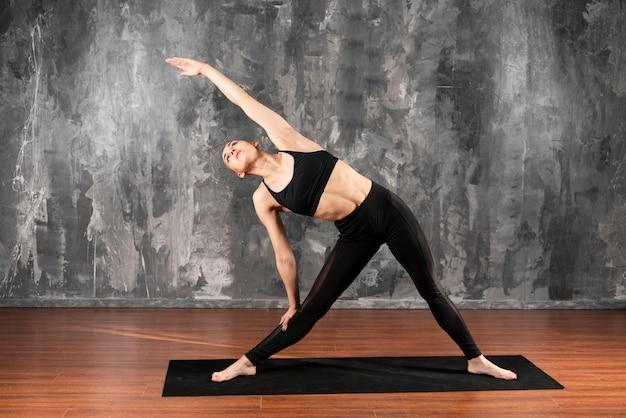 Donna della foto a figura intera che fa yoga all'interno