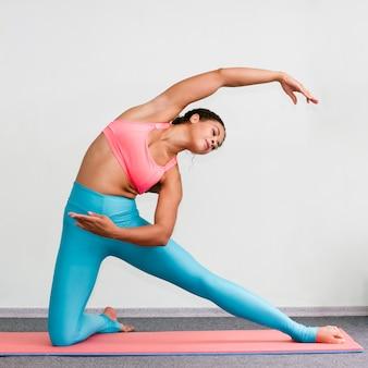 Donna della foto a figura intera che fa yoga con la stuoia