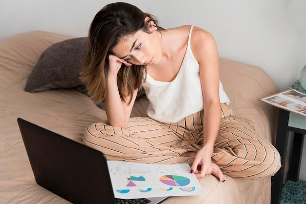 Donna della foto a figura intera che lavora a casa