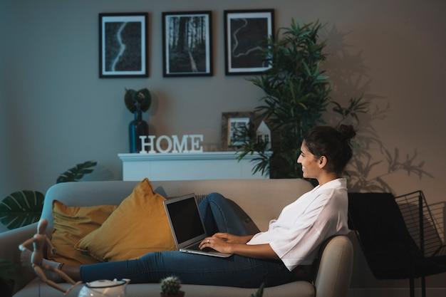 Donna della foto a figura intera che lavora al computer portatile a casa