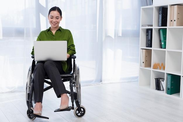 Donna della foto a figura intera che lavora al computer portatile
