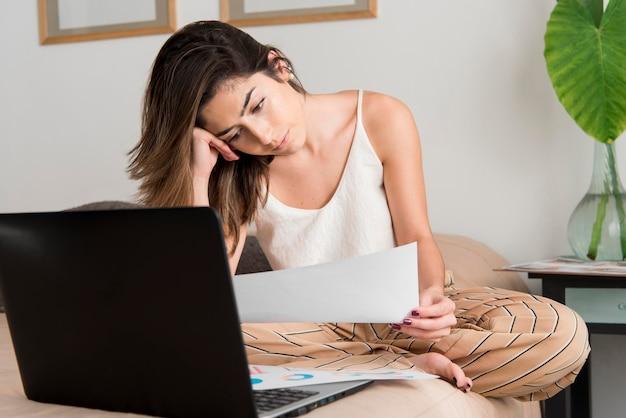 Donna della foto a figura intera che lavora nel letto