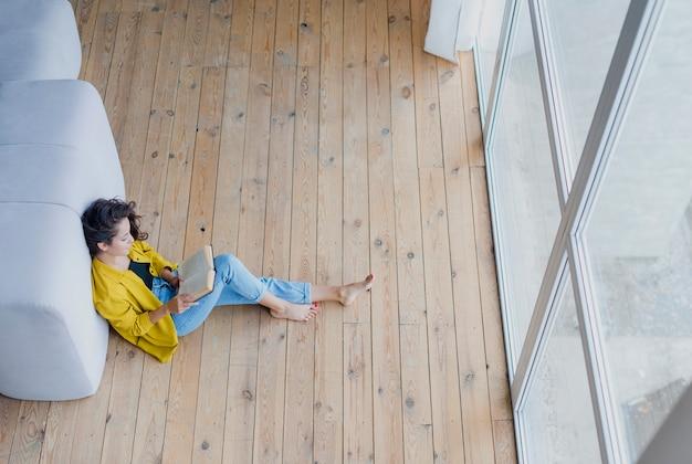 Donna della foto a figura intera che legge un libro sul pavimento
