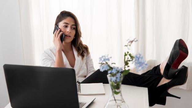 Donna della foto a figura intera che parla sul telefono